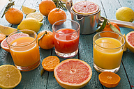 Glasses of orange juice, grapefruit juice and multivitamine juice, juice squeezer and fruits on wood - SARF001196
