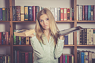 Woman with book and tablet pc in front of bookshelf, undecided - SAR001210