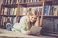 Woman using digital tablet, bookshelf in the background - SAR001212