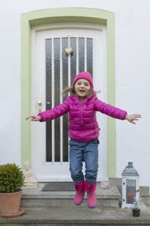 Young girl wearing pink warm clothing and jumping from step - MW000085