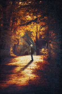 Germany, man standing on street in the morning light - DWI000374