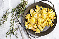 Cast iron frying pan of fried potatoes, thyme and cutlery on wood - ODF000923