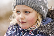 Portrait of blond little girl wearing wool cap and winter jacket - TCF004478