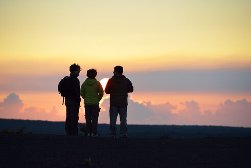 USA, Hawaii, Big Island, Volcanoes National Park, three persons watching sunset at Kilauea Iki - BRF000917