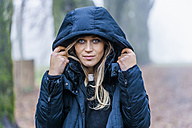 Portrait of blond woman wearing blue anorak - TCF004494