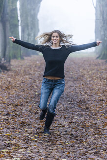 Woman with outstretched armes running along a forest track - TCF004495