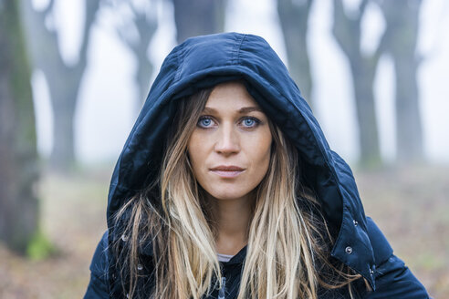Portrait of serious looking blond woman with blue hood - TCF004500