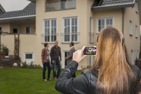Teenage girl photographing her parents and estate agent in front of residential house - PAF001118