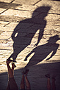 Italy, Venice, shadows of people on the pavement in morning light - EHF000039