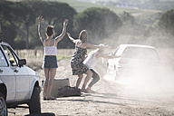 South Africa, Friends on a road trip stopping car for assistance with breakdown - ZEF002698
