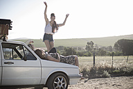 South Africa, Friends on a road trip resting on car bonnet - ZEF002702
