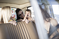 South Africa, Friends on road trip sitting in car with little girl - ZEF002709