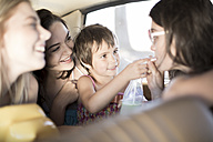 South Africa, Friends on road trip with little girl sharing drink - ZEF002712