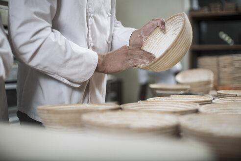 Baker preparing bread pans for baking bread - ZEF003773