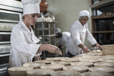 Bakers preparing ceramic bowls for baking bread - ZEF003788