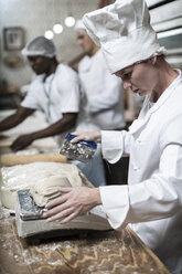 Female baker weighing dough and cutting it into correct sizes - ZEF003790