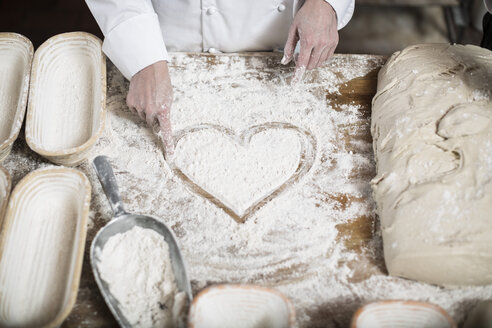 Female baker drawing heart in flour on a wooden table top - ZEF003793