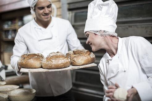 Female baker smelling fresh bread - ZEF003800