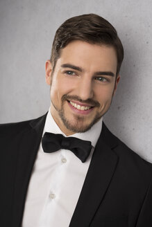 Portrait of smiling man wearing dinner jacket and bow - SHKF000107