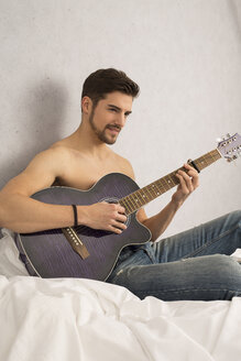 Shirtless man with guitar sitting on bed - SHKF000115