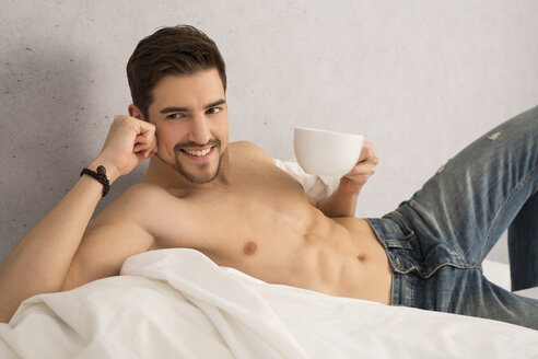 Shirtless man with cup of coffee lying on bed - SHKF000116