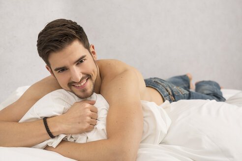 Portrait of shirtless man lying on bed - SHKF000117