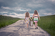 Germany, Bavaria, Two girl walking on country road carrying old suitcase, rear view - VTF000382