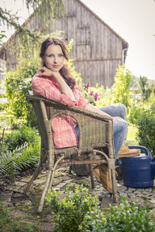 Germany, Coburg Young woman in garden sitting in wicker chair - VTF000385