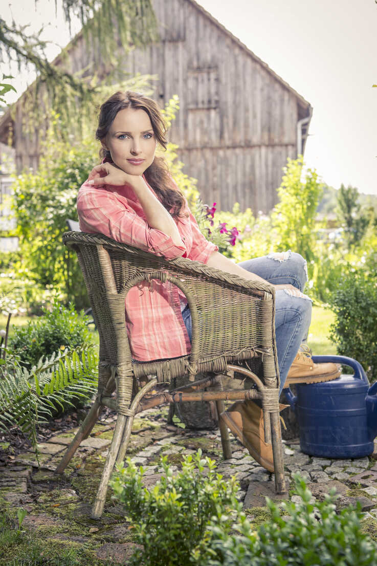 Germany, Coburg Young woman in garden sitting in wicker chair - VTF000385 - Val Thoermer/Westend61