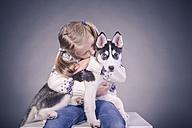 Blond girl holding husky puppy on lap - VT000386