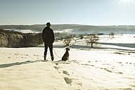Germany, Bergisches Land, man walking dog in winter landscape - ONF000753