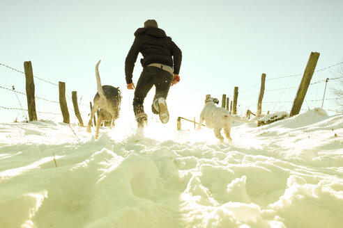 Germany, Bergisches Land, man running with dogs in winter landscape - ONF000739
