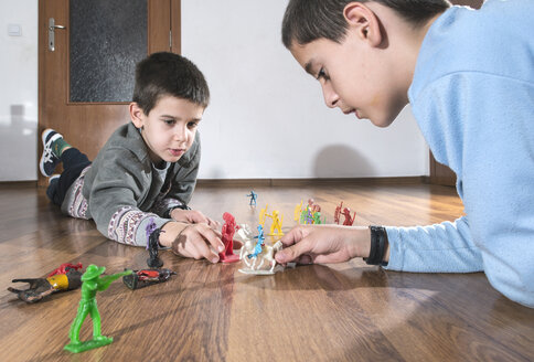 Two boys playing with miniature figurines on the floor at home - DEGF000103