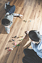 Two boys playing with miniature figurines on the floor at home - DEGF000104