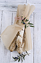 Wrapped home-baked baguettes with olives and dried tomatoes on wood - ODF000974