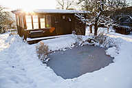 Garden with shed and pond in snow - NDF000509