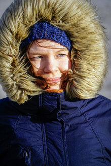 Portrait of smiling woman wearing wooly hat and fur cap - HOHF001264