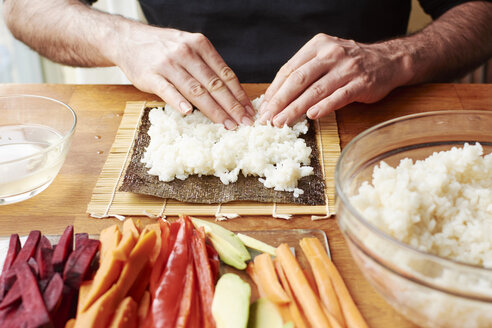 Man spreading rice on a nori sheet to make vegetable sushi - HAWF000563