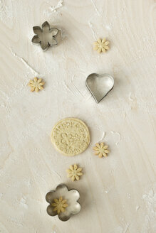Home-baked birthday cookies and metal cookie cutters on light wood - MYF000798