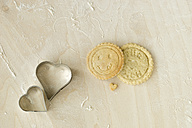 Home-baked motif cookies and heart shaped cookie cutters on light wood - MYF000800