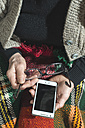 Senior woman holding glasses and smartphone, partial view - DEGF000111