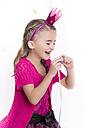Laughing little girl masquerade as a princess holding streamer - YFF000287
