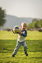 Boy holding ball on meadow - PAF001160