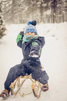 Germany, Bavaria, Berchtesgadener Land, happy boy on sledge - MJF001380