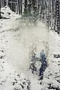 Germany, Bavaria, Berchtesgadener Land, snow falling on boy in woods - MJF001403