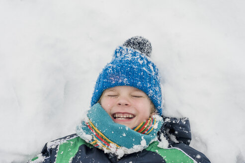 Germany, Bavaria, Berchtesgadener Land, happy boy lying in snow - MJF001429