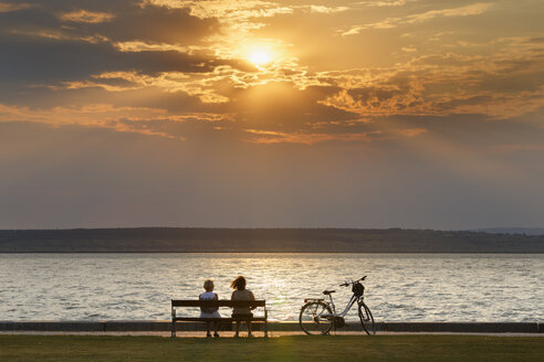 Austria, Burgenland, Illmitz, Lake Neusiedl, People sitting on bench at sunset - SIE006348