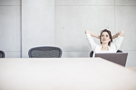 Businesswoman with laptop in conference room leaning back - ZEF003095