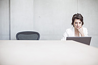 Businesswoman using laptop in conference room - ZEF003052