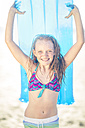 Girl on the beach smiling and holding a lilo - ZEF003303